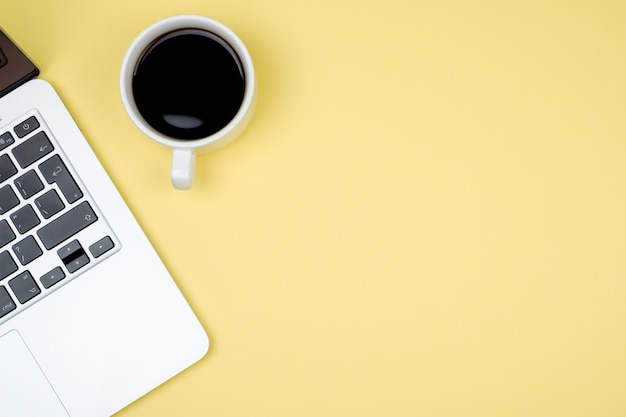 Bovenaanzicht van werkruimte met laptop, kopje koffie en kopie ruimte