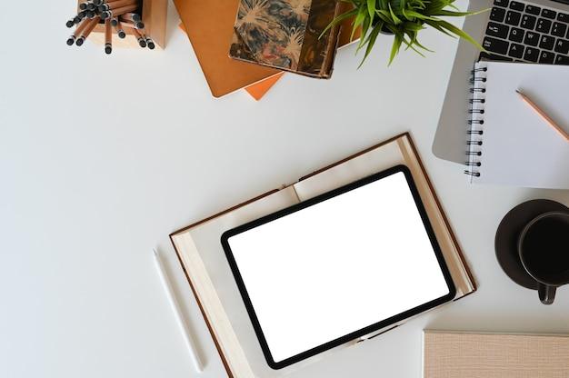 Bovenaanzicht van werkruimte met leeg scherm digitale tablet, vintage boek, notebook, kamerplant en kantoorbenodigdheden.