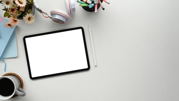 Bovenaanzicht van werkruimte met leeg scherm tablet, dagboek, koffiekopje, hoofdtelefoon en briefpapier op witte tafel.