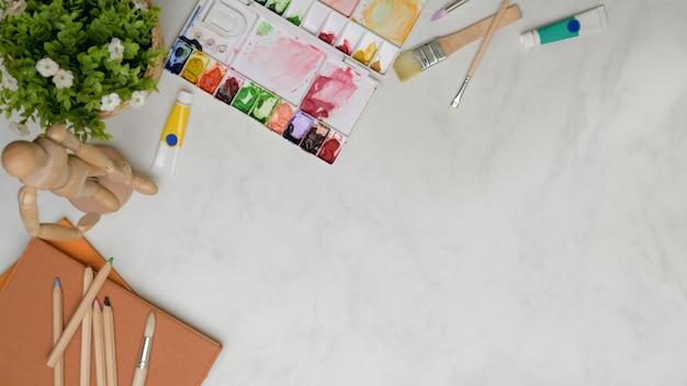 Bovenaanzicht van werkruimte met verfgereedschap, notitieboekjes, decoratie en kopie ruimte op marmeren tafel