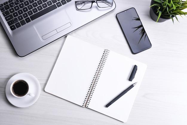 Bovenaanzicht van werkruimte op kantoor, houten bureau tafel met laptop notebook, toetsenbord pen, bril, telefoon, notebook en kopje koffie. met een kopie ruimte, plat leggen.