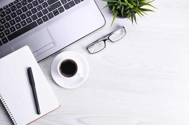 Bovenaanzicht van werkruimte op kantoor, houten bureautafel met laptop notebook, toetsenbord, pen, bril, telefoon, notitieboekje en kopje koffie