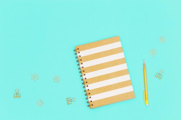 Bovenaanzicht van werktafel met gesloten schrift over veer, geel kleurpotlood, gouden metalen clips voor papier en documenten.