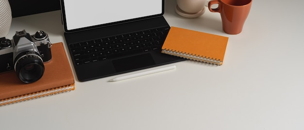 Bovenaanzicht van werktafel met tablet camera briefpapier en kopie ruimte in kantoor aan huis kamer