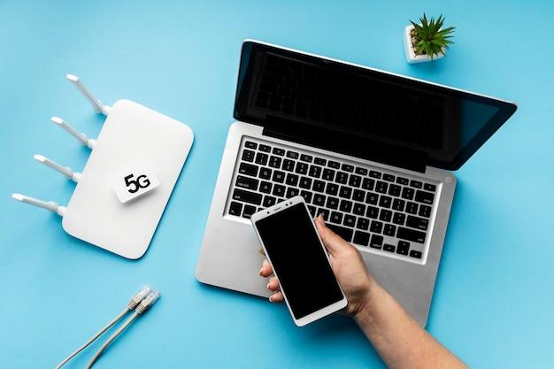 Bovenaanzicht van wifi-router met laptop en hand met smartphone