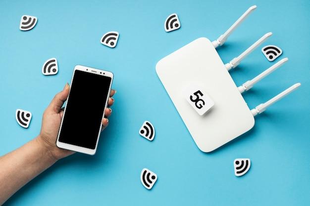 Bovenaanzicht van wifi-router met smartphone en 5g-symbool