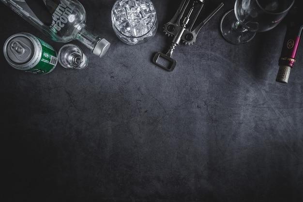 Bovenaanzicht van wijnfles, wodka fles, ijsblokje, bier en kurkentrekker