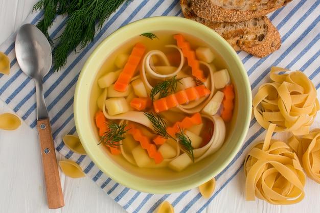Bovenaanzicht van winter groentesoep in kom met tagliatelle en toast