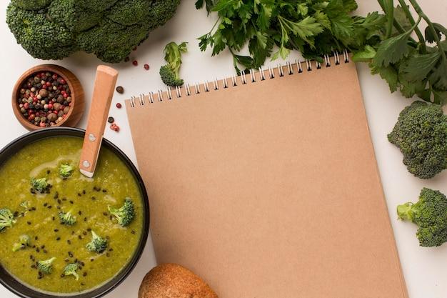 Bovenaanzicht van winterbroccolisoep in kom met notitieboekje
