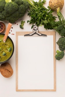 Bovenaanzicht van winterbroccolisoep met blocnote en selderij