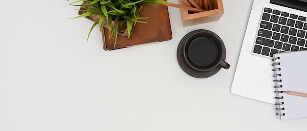 Bovenaanzicht van wit bureau met koffie, laptop en notebook.