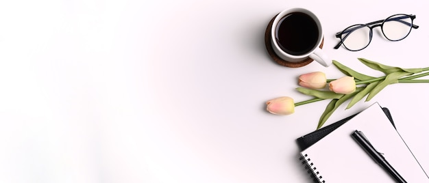 Bovenaanzicht van wit bureau met koffiekopje, bril, notitieboekje, bloemen en kopieerruimte.