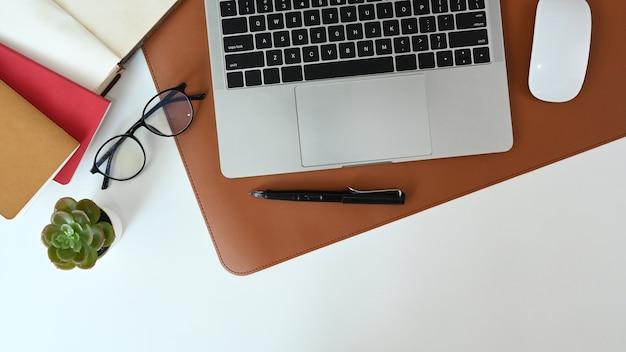 Bovenaanzicht van wit bureau met laptopcomputer, bril, notebook en plant.