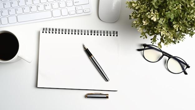 Bovenaanzicht van wit bureau met lege notebook, glazen, kamerplant, koffiekopje en pen.