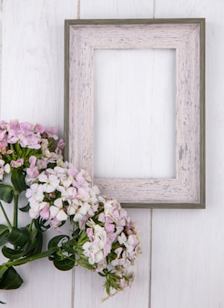Bovenaanzicht van wit frame met bloemen op een wit oppervlak