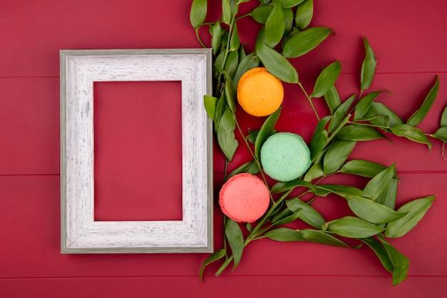 Bovenaanzicht van wit frame met kleurrijke macarons en bladtakken op een rood oppervlak