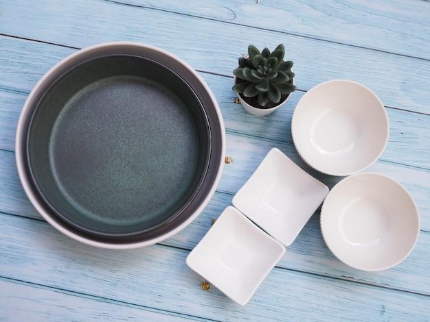 Bovenaanzicht van wit keramiek servies met kom plaat of ronde schotel en serviesgoed op houten tafel.