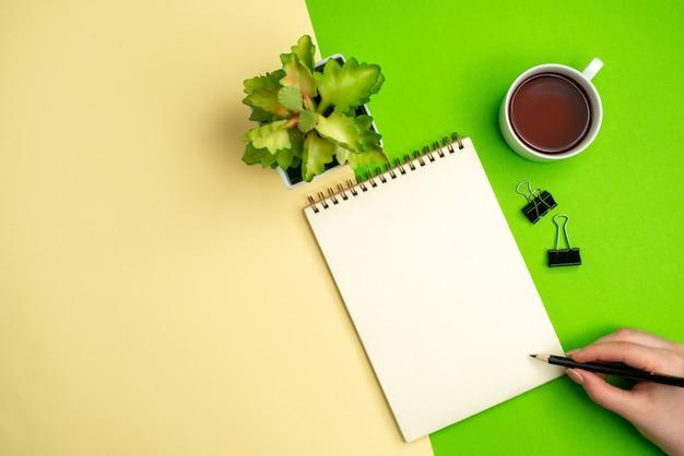 Bovenaanzicht van wit notitieboekje met pen naast een kopje thee bloempot op witte en gele achtergrond