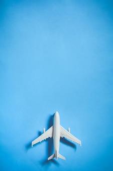 Bovenaanzicht van wit speelgoedvliegtuigmodel over de blauwe kleurachtergrond met concept van reizen