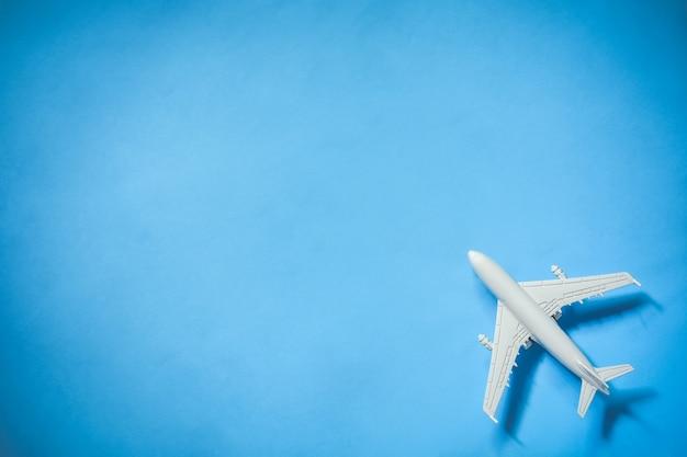 Bovenaanzicht van wit speelgoedvliegtuigmodel over het blauwe kleurachtergrondconcept van reizen