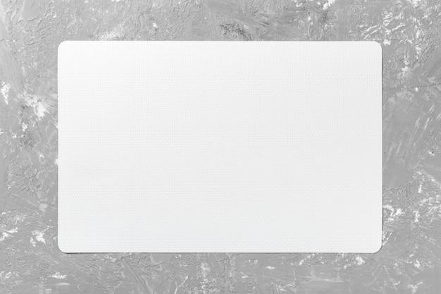 Bovenaanzicht van wit tafellaken voor voedsel op cement achtergrond. lege ruimte voor uw ontwerp