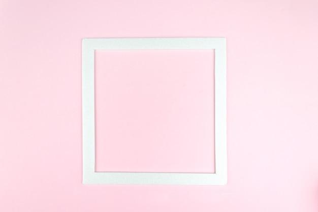 Bovenaanzicht van wit vierkant frame op roze, minimalistisch concept. vierkant leeg kaartmodel.