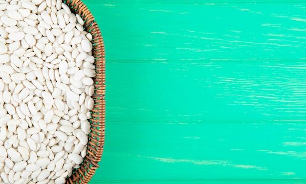 Bovenaanzicht van witte bonen in rieten mand op groene houten achtergrond met kopie ruimte