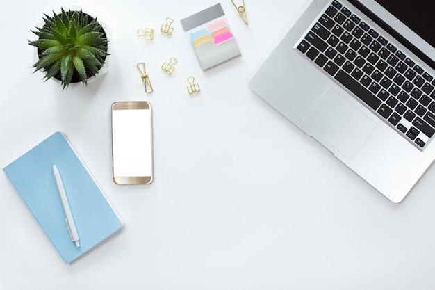 Bovenaanzicht van witte bureau tafel met laptop, laptop, mobiele telefoon, groene bloem en accessoires, plat lag. bovenaanzicht met kopie ruimte.