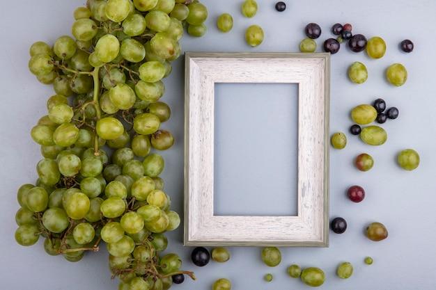 Bovenaanzicht van witte druif en frame met druivenbessen op grijze achtergrond met kopie ruimte