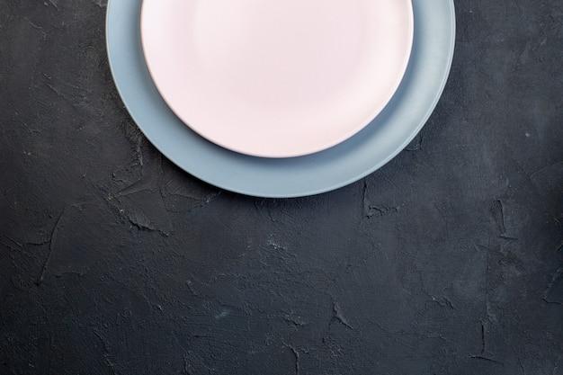 Bovenaanzicht van witte en blauwe keramische lege platen op zwarte achtergrond met vrije ruimte