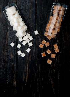 Bovenaanzicht van witte en bruine suikerklontjes verspreid uit glazen potten op donkere houten achtergrond met kopie ruimte