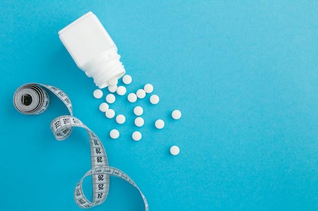 Bovenaanzicht van witte fles, pillen en centimeter