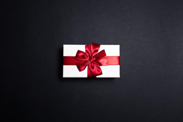 Bovenaanzicht van witte geschenkdoos met rode strik op zwarte ondergrond