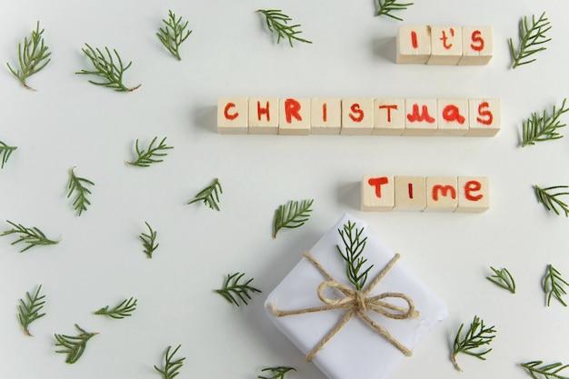 Bovenaanzicht van witte handgemaakte geschenkdoos met houten tekstletters van de kersttijd en verse sparrentak