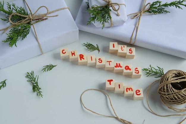 Bovenaanzicht van witte handgemaakte geschenkdozen met de tekst van de kersttijd, houten letters en verse dennenzemelen