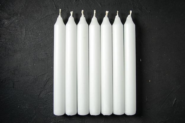 Bovenaanzicht van witte kaarsen op de donkere muur