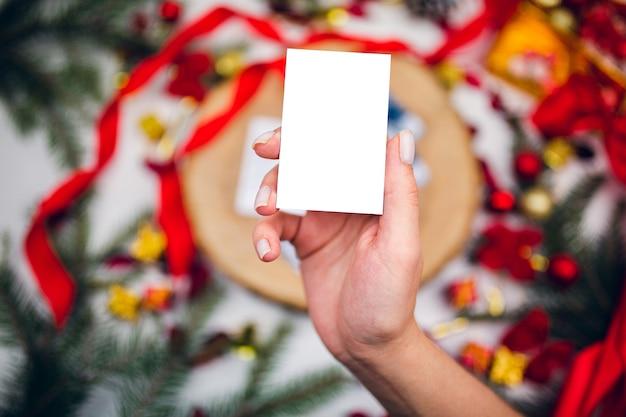 Bovenaanzicht van witte kaart, mockup in vrouwelijke hand op feestelijke achtergrond