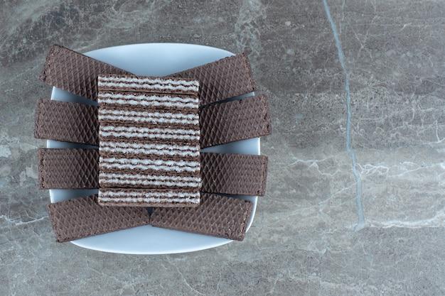 Bovenaanzicht van witte keramische kom vol met chocoladewafels.