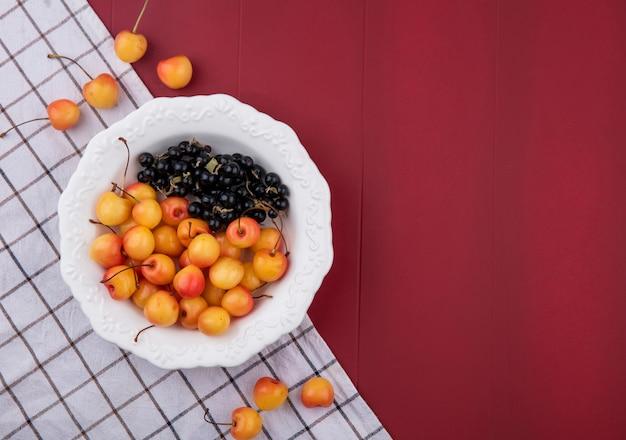 Bovenaanzicht van witte kers met zwarte bessen op een bord met een geruite handdoek op een rood oppervlak
