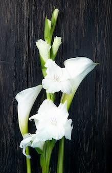 Bovenaanzicht van witte kleur gladiolen en calla lelie bloemen geïsoleerd op zwarte achtergrond