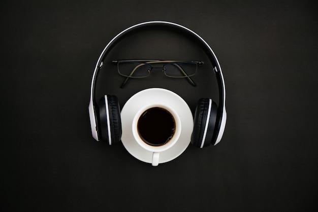 Bovenaanzicht van witte koffiekopje met hoofdtelefoon en leraar bril op zwart papier achtergrond.