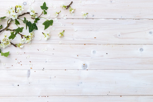 Bovenaanzicht van witte lentebloemen en bladeren op een houten tafel met ruimte voor uw tekst