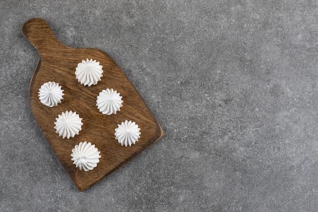 Bovenaanzicht van witte meringue cookies op een houten bord.