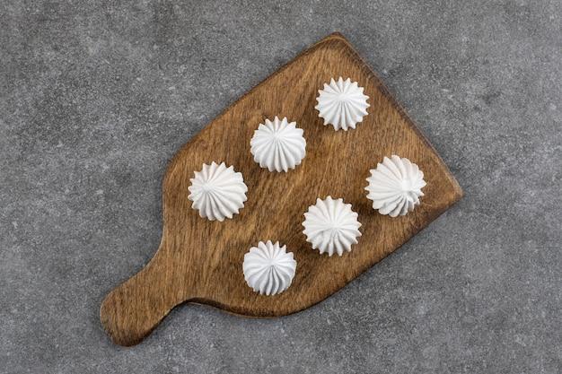 Bovenaanzicht van witte meringue cookies op houten snijplank.
