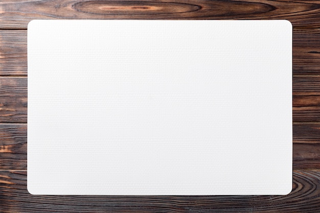 Bovenaanzicht van witte placemat voor een schotel. houten tafel