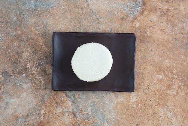 Bovenaanzicht van witte ronde kaas op donkere plaat op marmer