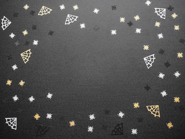 Bovenaanzicht van witte spinnen en gele webvorm op zwarte grungetextuur voor halloween-achtergrondconcept.