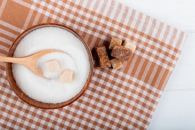 Bovenaanzicht van witte suiker in een houten kom met een lepel en stukjes suiker en palmsuiker stukken op geruite tafellaken met kopie ruimte