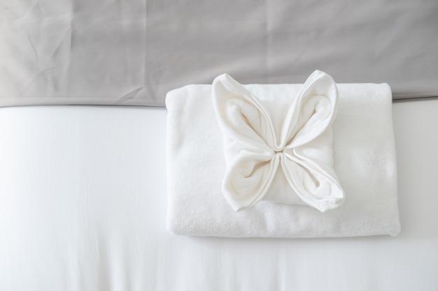 Bovenaanzicht van witte verse handdoek op bed