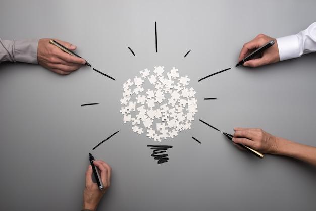 Bovenaanzicht van witte verspreid puzzelstukjes en ondernemers handen